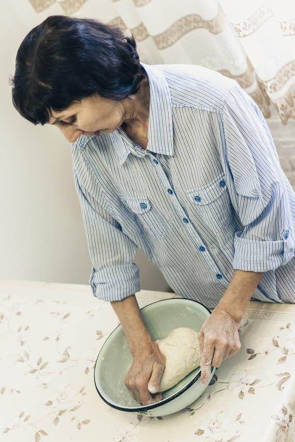 Donna castana di mezza età che impasta producendo pasta per gli gnocchi in ciotola blu fotografia stock libera da diritti