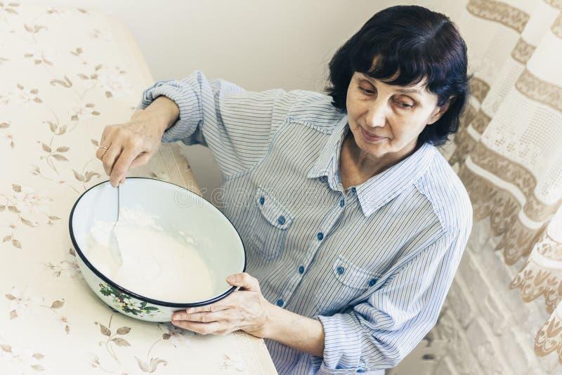 Donna castana di mezza età che impasta producendo pasta per gli gnocchi in ciotola blu fotografie stock libere da diritti
