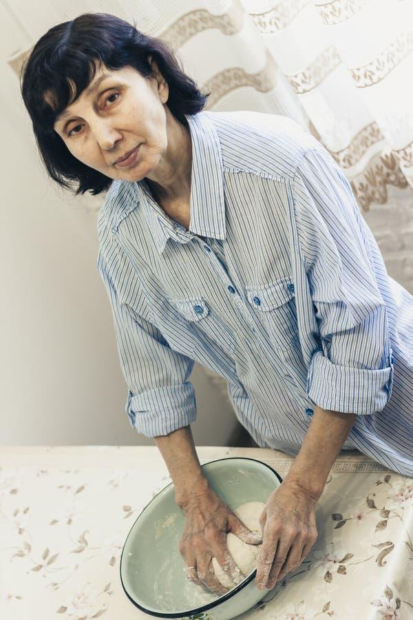 Donna castana di mezza età che impasta producendo pasta per gli gnocchi in ciotola blu immagine stock libera da diritti