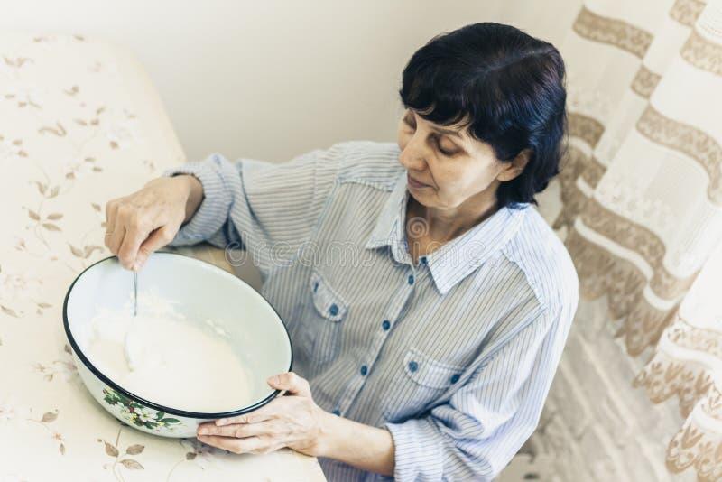 Donna castana di mezza età che impasta producendo pasta per gli gnocchi in ciotola blu fotografie stock
