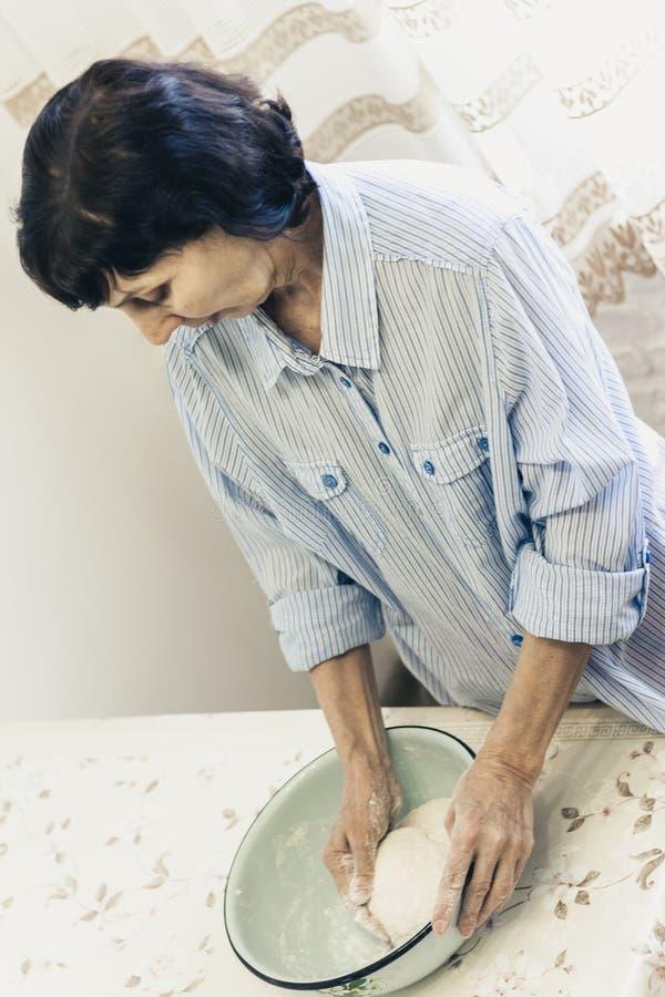 Donna castana di mezza età che impasta producendo pasta per gli gnocchi in ciotola blu immagini stock