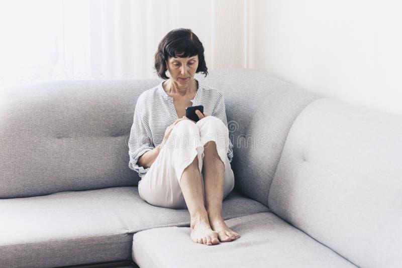 Donna castana di mezza età con i vetri sullo smartphone grigio di uso del sofà fotografia stock libera da diritti