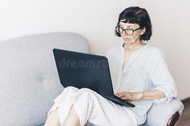 Donna castana di mezza età in vetri sul sofà grigio facendo uso del computer portatile fotografia stock