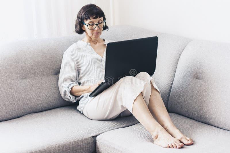 Donna castana di mezza età in vetri sul sofà grigio facendo uso del computer portatile immagine stock