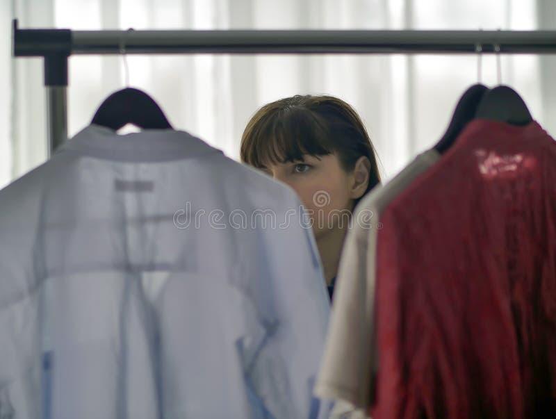 Donna castana graziosa che considera i vestiti sui ganci immagini stock libere da diritti