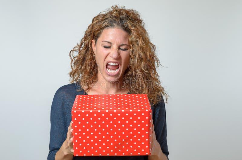 Donna castana gridante che tiene il contenitore di regalo rosso fotografie stock