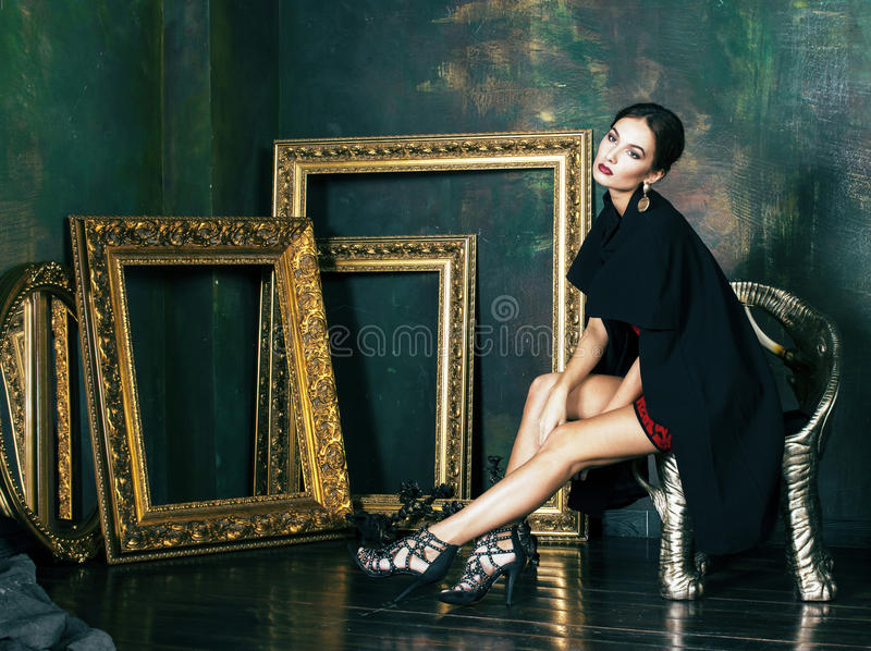 Donna castana ricca di bellezza nei telai vuoti vicini interni di lusso, immagine stock