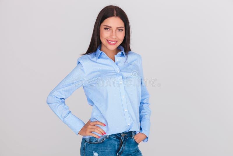 Donna castana rilassata che porta una camicia blu ed i jeans immagine stock