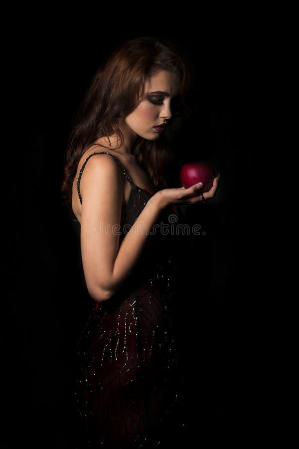 Donna castana sexy con il vestito rosso scuro che esamina giù la mela rossa in sua mano immagine stock libera da diritti