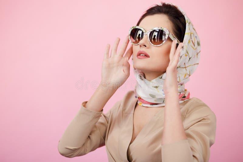 Donna castana sicura alla moda che tocca i suoi occhiali da sole, durando in sciarpe, cercando, isolato su un fondo rosa fotografia stock