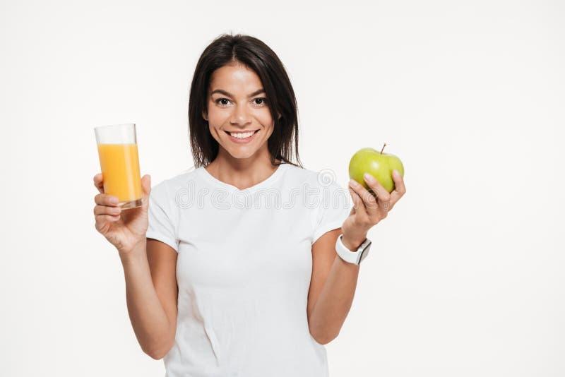 Donna castana sorridente che tiene vetro di un succo d'arancia fotografia stock libera da diritti