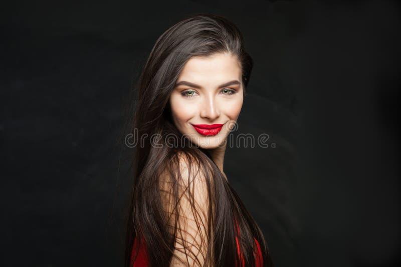Donna castana sorridente con capelli sani diritti lunghi su fondo nero fotografia stock