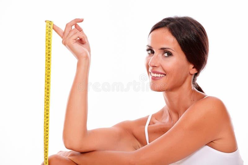 Donna castana sorridente con la misura di nastro immagini stock
