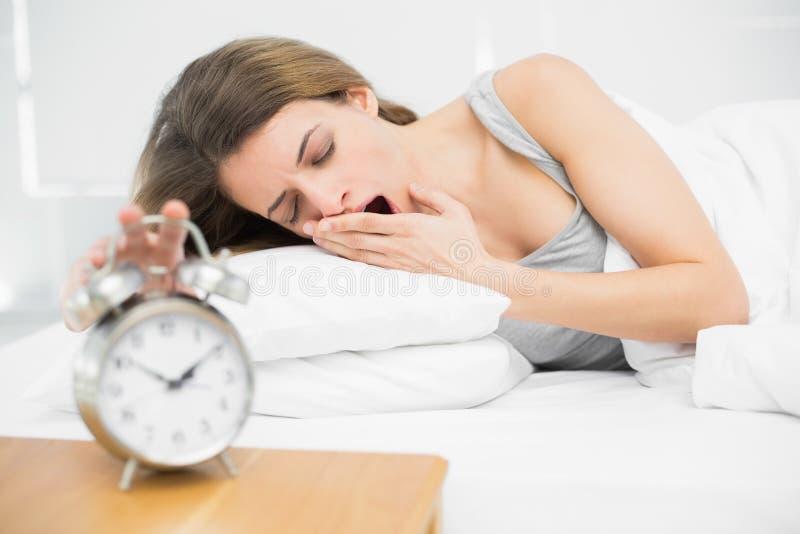 Donna castana stanca che spegne la sveglia mentre sbadigliando fotografie stock libere da diritti