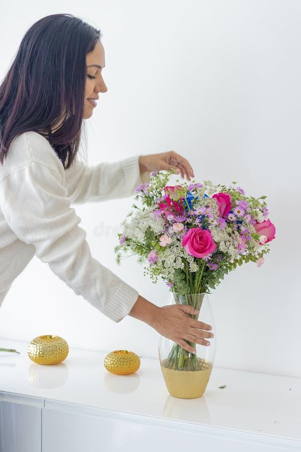 Donna castana sveglia che gode del suo mazzo dei fiori fotografia stock