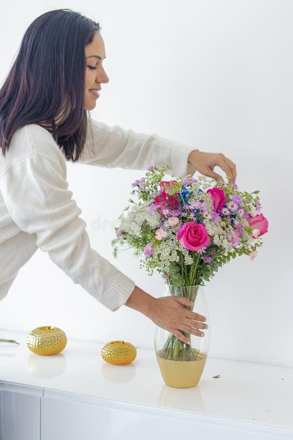 Donna castana sveglia che gode del suo mazzo dei fiori immagine stock