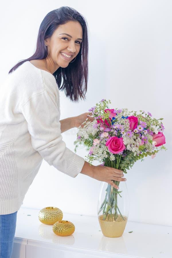 Donna castana sveglia che gode del suo mazzo dei fiori fotografia stock libera da diritti