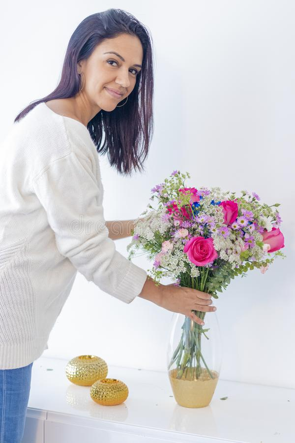 Donna castana sveglia che gode del suo mazzo dei fiori immagini stock