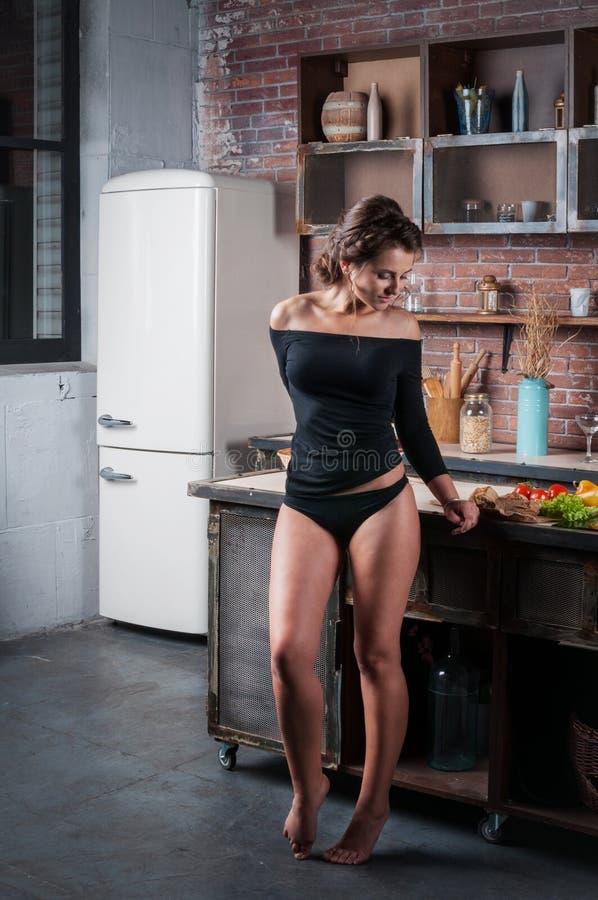 Donna castana in un bikini nero che posa nella cucina for Posa alzatina cucina