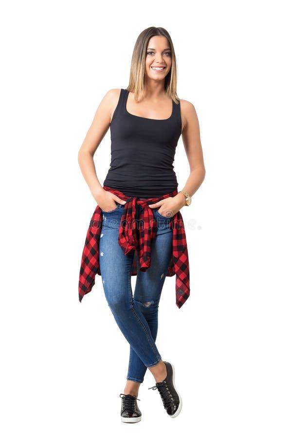Donna casuale abbastanza giovane con la camicia legata intorno alla vita ed alle mani nel sorridere delle tasche fotografia stock libera da diritti