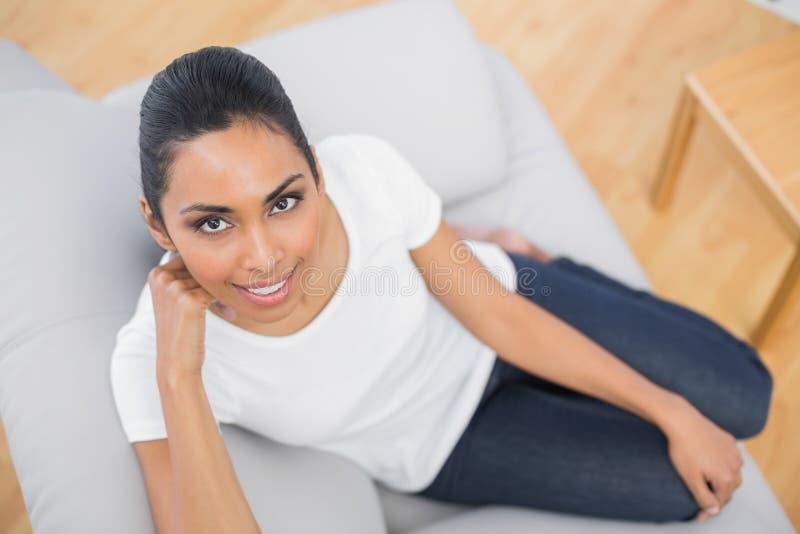 Donna casuale adorabile che sorride alla macchina fotografica che si siede sullo strato fotografia stock libera da diritti