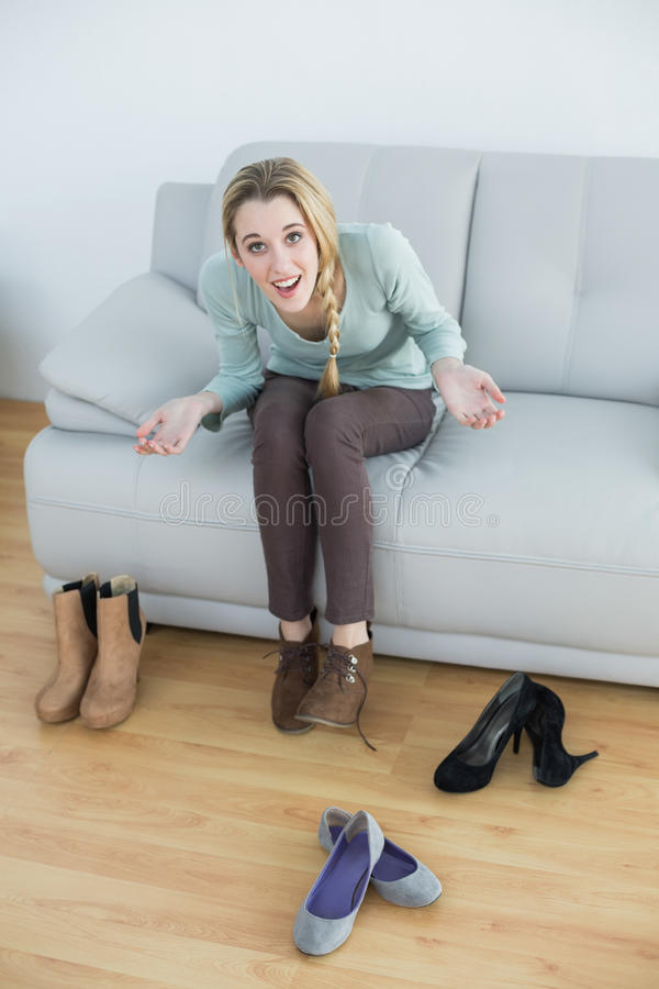 Donna casuale allegra che lega i suoi laccetti che si siedono sullo strato fotografia stock