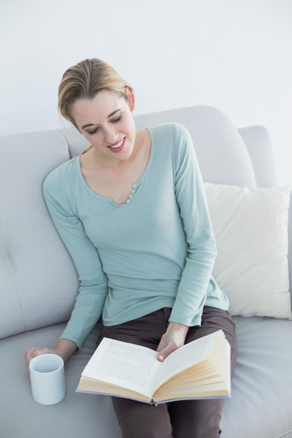 Donna casuale allegra che legge un libro che tiene una tazza fotografia stock libera da diritti