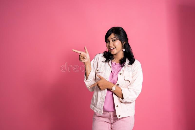 Donna casuale che indica il copyspace dal lato fotografie stock libere da diritti