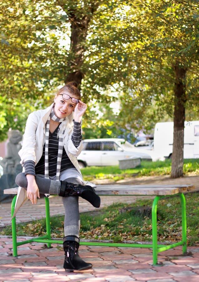 Donna casuale che si siede sul banco in sosta immagine stock