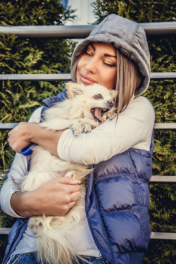 Donna casuale che tiene piccolo cane bianco fotografia stock libera da diritti