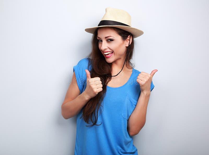 Donna casuale ottimista nella cima blu e cappello che mostra pollice su vicino immagine stock libera da diritti