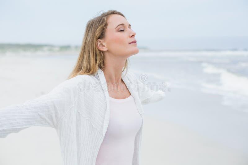 Donna casuale pacifica con gli occhi chiusi alla spiaggia immagini stock