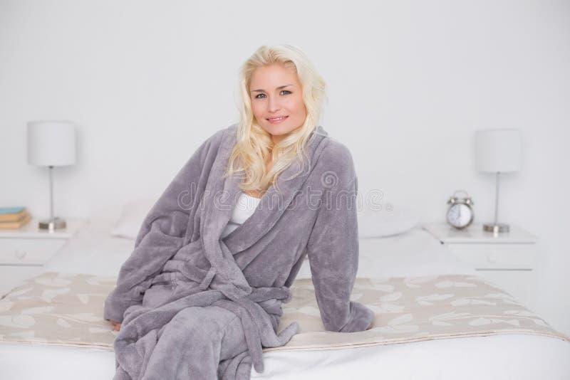 Donna casuale sorridente in accappatoio che si siede sul letto fotografia stock