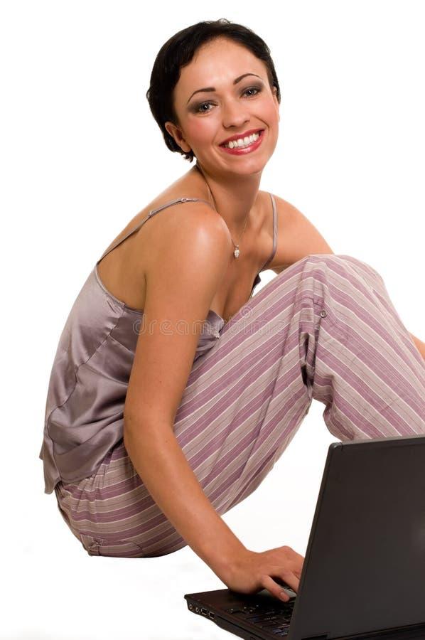 Donna casuale sul computer portatile fotografia stock
