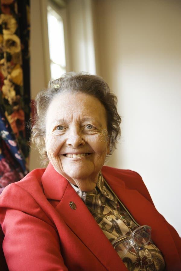Donna caucasica anziana dalla finestra. immagine stock