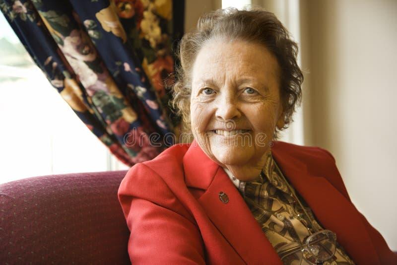 Donna caucasica anziana dalla finestra. fotografia stock