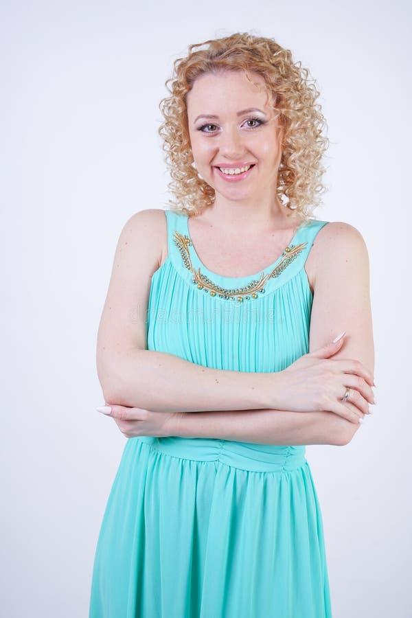 Donna caucasica bionda graziosa che porta il vestito blu lungo da estate di modo su fondo bianco fotografia stock