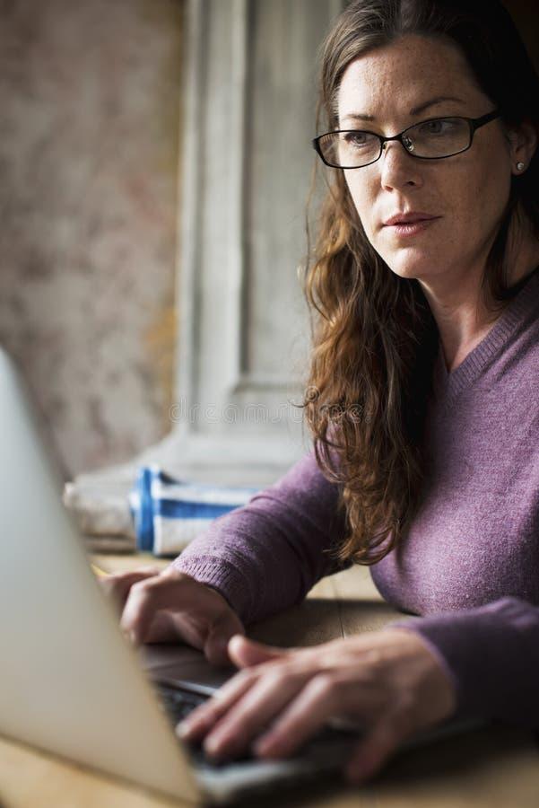 Donna caucasica che per mezzo del computer portatile del computer immagini stock libere da diritti