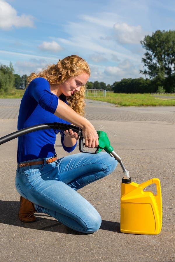 Donna caucasica che rifornisce tanica di combustibile con benzina fotografia stock libera da diritti