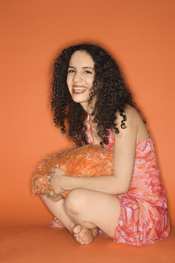 Donna caucasica che si siede sul pavimento con il cuscino. fotografia stock libera da diritti