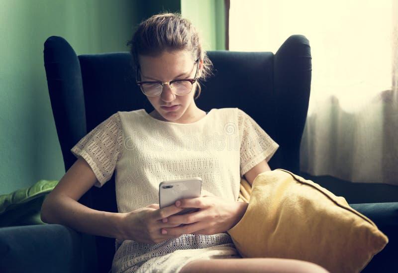 Donna caucasica che utilizza telefono nel salone immagini stock