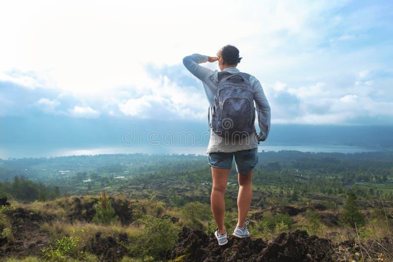 Donna caucasica con lo zaino che sta sopra una montagna e che guarda lontano sul paesaggio fotografie stock libere da diritti