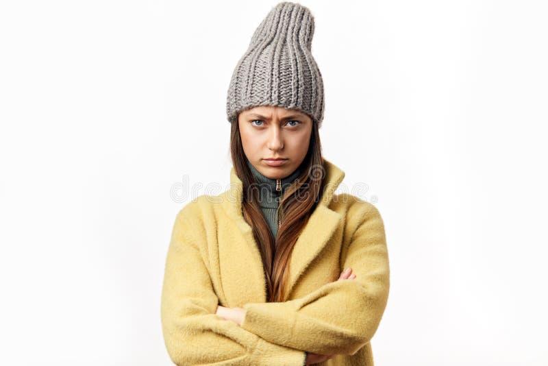 Donna caucasica confusa ed offensiva in vestiti variopinti di inverno che posano all'interno fotografie stock libere da diritti