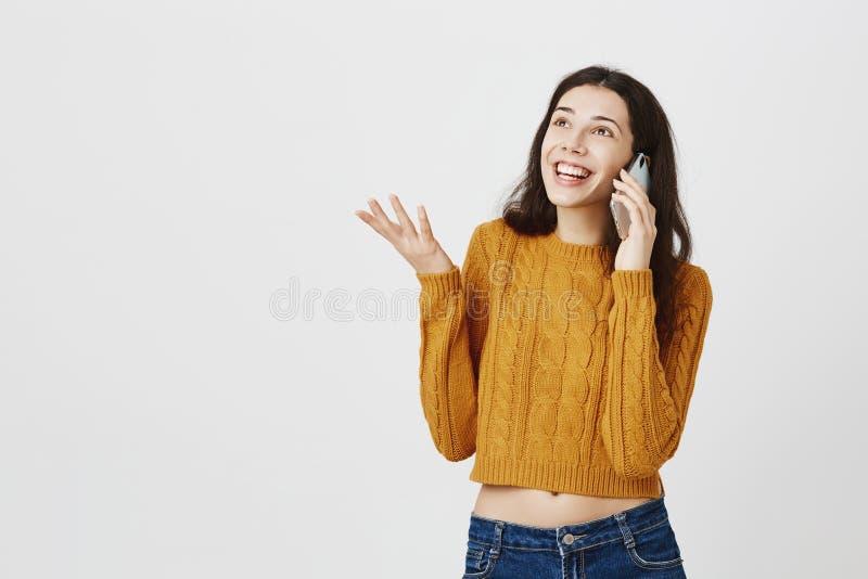 Donna caucasica d'avanguardia felice che parla con l'eccitazione via lo smarpthone, gesticolante come se spiegando qualcosa o fotografia stock