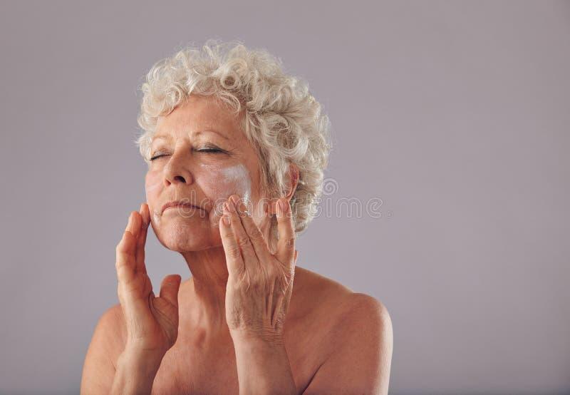 Donna caucasica matura che applica la crema di fronte della anti-grinza fotografia stock libera da diritti