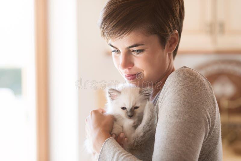 Donna che abbraccia il suo gattino immagini stock