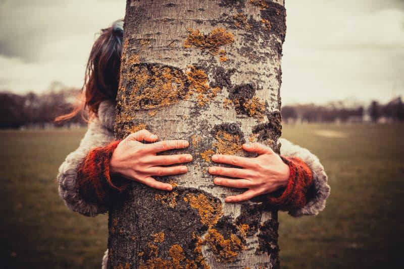 Donna che abbraccia un albero fotografie stock