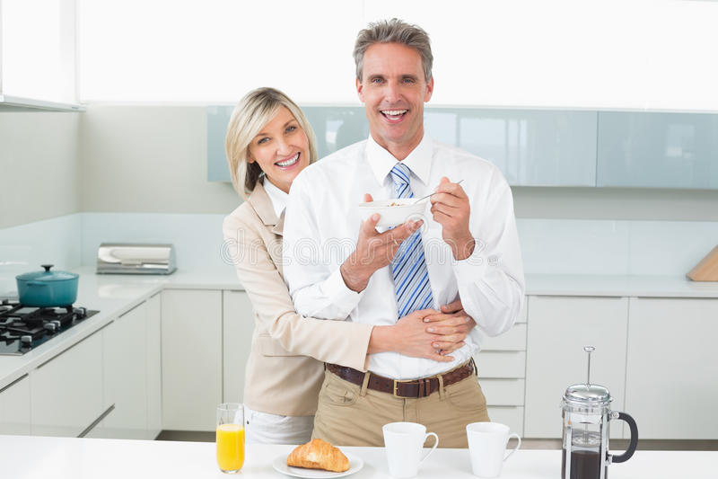 Donna che abbraccia un uomo felice da dietro in cucina fotografie stock