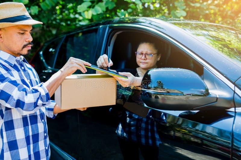 Donna che aggiunge il segno della firma sulla compressa dopo l'accettazione per ricevere le scatole dal fattorino in automobile n fotografie stock
