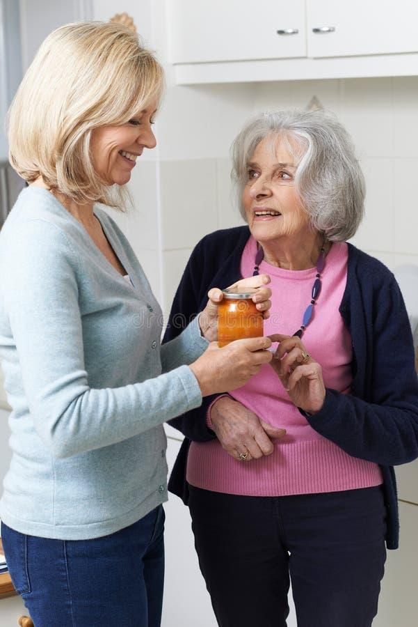 Donna che aiuta vicino senior a rimuovere il coperchio del barattolo immagini stock